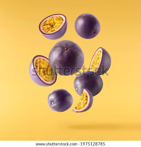 Fresh ripe raw passion fruit falling in the air isolated on yellow background. Zero gravity and food levitation concept. High resolution Foto stock ©