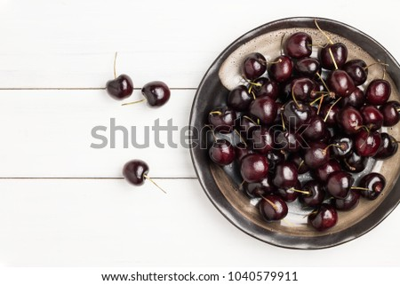 Fresh ripe red and black cherries in black ceramic dish in Japanese style on white wood plank floor for background. Top view point with copy space. #1040579911