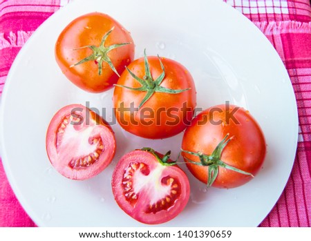 Fresh ripe ripe red tomatoes and cut tomato with water drops and green peduncle on white plate - top view, organic vegetables #1401390659