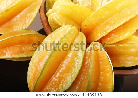 Fresh ripe star fruit in a wooden bowl
