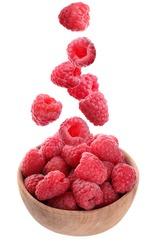 Fresh ripe tasty raspberries falling into bowl on white background
