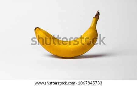 Fresh ripe wet banana fruit water drops on gray background