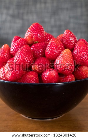 Fresh riped strawberries in a bowl on wooden table with low key scene #1324301420