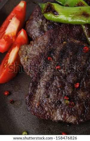fresh roast beef fillet mignon on old retro style cast iron pan on retro wooden table as background with rosemary peppercorn and tomatoes