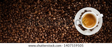 Fresh roasted coffee bean background with a cup of hot frothy espresso placed to the right side in a wide panorama banner with copy space #1407559505