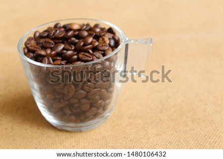 fresh roasted coffee beans in small glass cup, cup full of dark coffee beans on the cloth sack, glass cup, clear cup, drink, coffee lover #1480106432