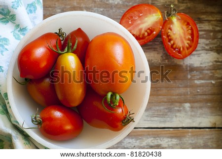 Fresh Roma and Juliet tomatoes, picked fresh from the garden, grouped in a white bowl. A vintage napkin accents the bright red color of the tomatoes.