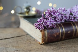 Fresh romantic, lilac  flowers on  antique book with candlestick  on old wooden background, soft focus.  Vintage, rustic, grunge, style. Celebration, Mothers day, memory card, appreciation symbol.