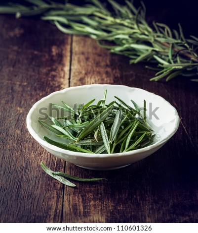 Fresh rosemary leaves in a bowl - stock photo