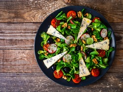 Fresh salad - blue cheese and vegetables on wooden table
