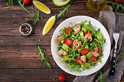Fresh salad bowl with shrimp, tomato, avocado and arugula on wooden background close up. Healthy food. Clean eating. Top view. Flat lay.
