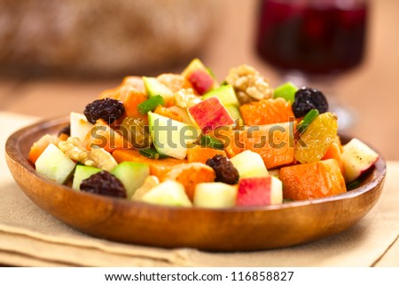 Fresh salad made of cooked sweet potatoes, fresh apples, nuts, raisins and shallots on wooden plate with mulled wine in the back (Selective Focus, Focus one third into the salad)