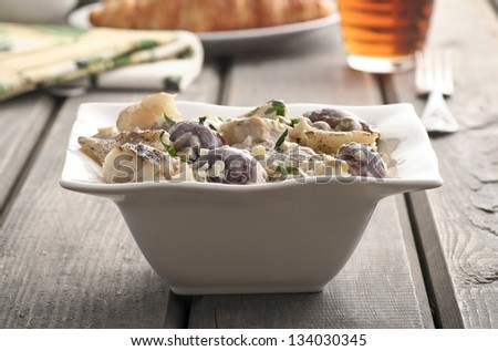 Fresh salad made of fish, vegetables and fruits in white bowl, standing on wooden vintage table in soft light. Selective focus.