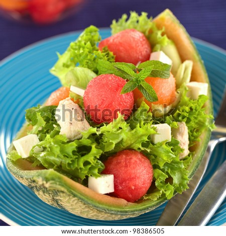 Fresh salad made of watermelon, cantaloupe melon, chicken, cucumber, cheese and lettuce (Selective Focus, Focus on the front of the mint leaf and the watermelon ball below it)
