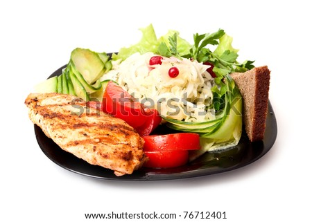 Fresh salad, meat, bread on black plate on white background