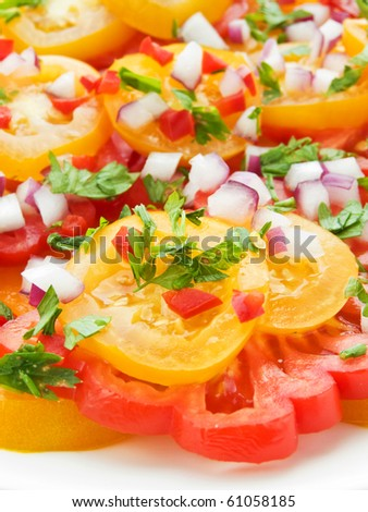 Fresh salad of colorful tomatoes, onion and herbs. Shallow dof.