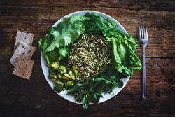 Fresh salad of vegetables and greens on a plate on a wooden background. Salad consists of Sprouted buckwheat grains, Finely chopped dill, zucchini, avocado, lettuce, spinach, Arugula and basil leaves