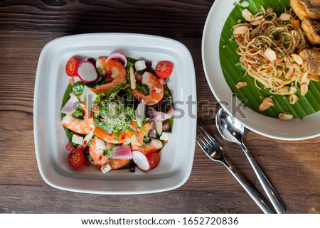Fresh salad plate with shrimp, tomato and mixed greens and blurred spaghetti side dish  on wooden background . Selective focus.Healthy food. Clean eating.