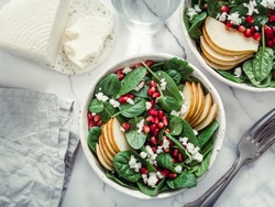 Fresh salad with baby spinach, pear, pomegranate and cottage cheese. Two bowls with delicious summer fruit salad on marble table. Copy space for text. Ideas and recipes for healthy breakfast or lunch