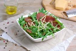 Fresh salad with bresaola, arugula, parmesan and pepper