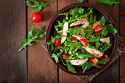 Fresh salad with chicken breast, arugula and tomato. Top view