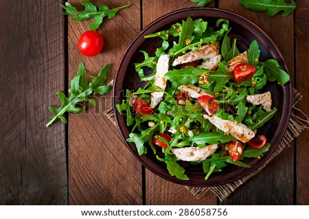 Fresh salad with chicken breast, arugula and tomato. Top view #286058756