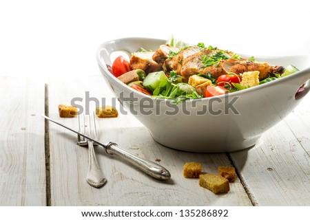Fresh salad with chicken on white background