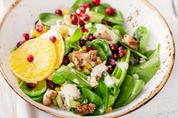 Fresh salad with chicken, orange and pomegranate seeds. Healthy diet food concept. View from above