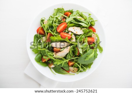 Fresh salad with chicken, tomato and greens (spinach, arugula) top view. Healthy food. #245752621