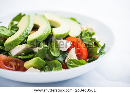 Fresh salad with chicken, tomatoes, spinach and avocado on white background close up. Healthy food.