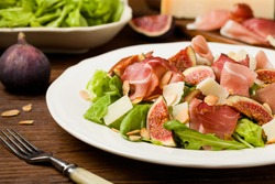 Fresh salad with figs and prosciutto with parmesan cheese and toasted almonds. Front view.