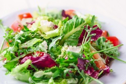Fresh salad with green and purple lettuce, tomatoes and cucumbers on white wooden background close up. Healthy food.