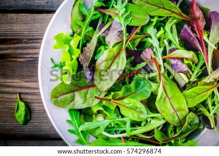 Fresh salad with mixed greens in bowl on wooden background closeup