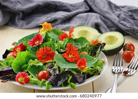 Fresh salad with Nasturtium flowers, cherry tomatoes and avocado. Selective focus with extreme shallow depth of field.   #680240977