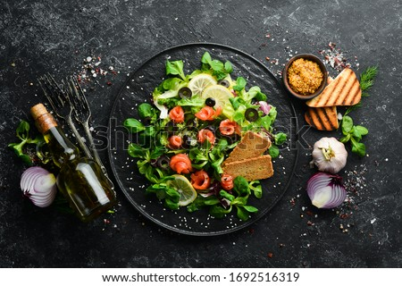 Fresh salad with salmon and olives in black plate. Top view. Free space for your text. Rustic style.