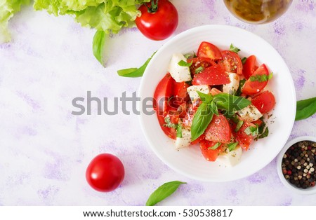 Shutterstock Fresh salad with tomato, mozzarella and basil. Top view.