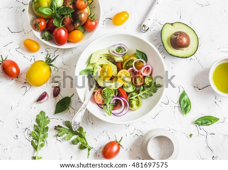 Fresh salad with tomatoes and avocado on a light background. Top view
