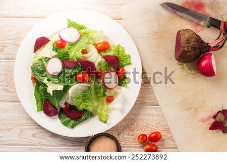 Fresh salad with tomatoes and beetroot Top view on wood table