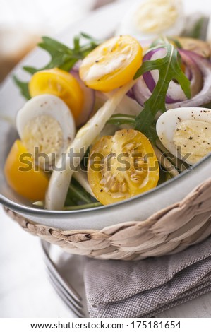 Fresh salad with yellow cherry tomatoes, fennel and quail eggs