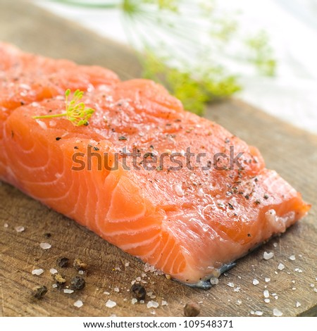 Fresh salmon fillet on wooden board, selective focus