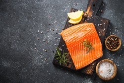 Fresh Salmon fish. Uncooked salmon fillet with ingredients for cooking on black stone table. Top view with copy space.