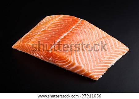 fresh salmon steak over black background