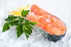 fresh salmon steak with parsley and lemon slices on ice