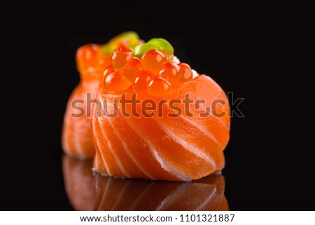 Fresh salmon sushi rolls with caviar isolated on black background.