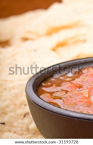 fresh salsa in a black bowl and corn chips