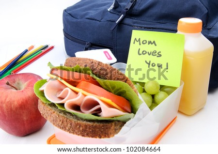 Fresh sandwich and apple with schoolbag and post-it note