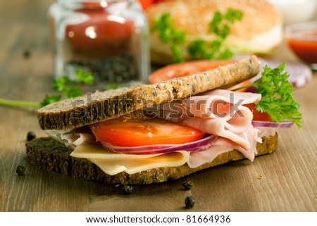 Fresh sandwich with cheese, ham and tomato on wooden table