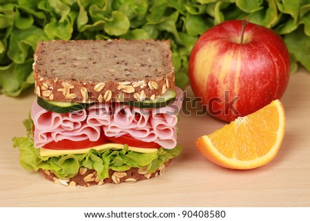 Fresh sandwich with ham, cheese and lettuce, orange and apple on a wooden table