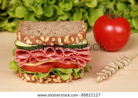 Fresh sandwich with salami, cheese and lettuce on a wooden table