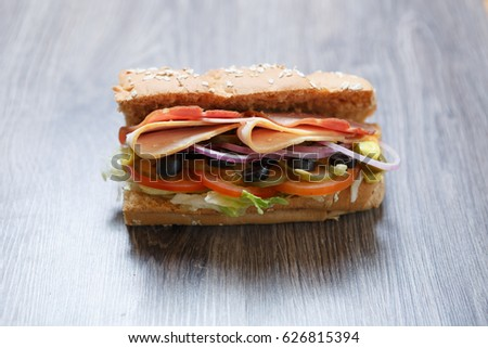 Fresh sandwich with tomato,ham & parmesan cheese slice,black olives & mustard sauce on table in cafe.Fast food restaurant menu close up.Delicious street food dish